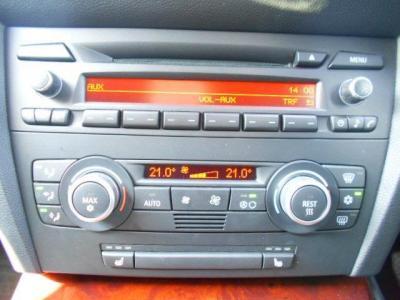 左右独立で温度調節可能なオートエアコンに、自然な音質が楽しめるCDの純正デッキ。ひじ掛けの下には小物入れの他に携帯音楽プレイヤー接続用のAUX端子が装備されています。